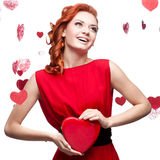 Fille red-haired de sourire retenant le coeur rouge Image stock