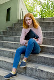 Fille Red-haired s'asseyant sur les escaliers photos stock