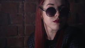 Fille Redhaired dans de grandes lunettes de soleil posant devant le mur de briques dans la chambre noire banque de vidéos