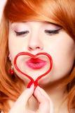 Fille Redhaired tenant le baiser de soufflement d'amour de coeur Photographie stock libre de droits