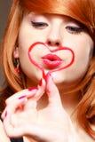 Fille Redhaired tenant le baiser de soufflement d'amour rouge de coeur. Jour de valentines. Photographie stock libre de droits