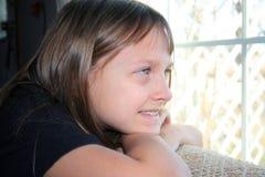 Fille regardant à l'extérieur l'hublot avec un sourire. Photo libre de droits