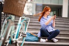 Fille regardant dans le téléphone portable tout en faisant une pause en ville photographie stock libre de droits