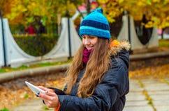 Fille regardant dans un comprimé avec un sourire sur son visage Photos libres de droits