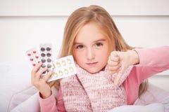 Fille regardant des pilules de froid et de grippe photo stock