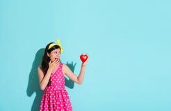 Fille regardant en forme de coeur à l'arrière-plan bleu Photographie stock libre de droits