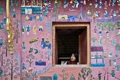 Fille regardant hors de l'hublot avec le beau mur Image stock