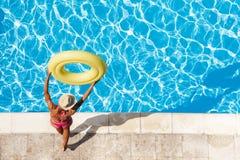Fille regardant l'eau bleue se tenant à côté de la piscine Photos stock