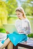 Fille regardant l'ordinateur portable se reposant sur le banc le parc extérieur Photo stock