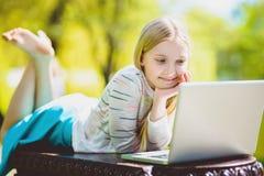 Fille regardant l'ordinateur portable se trouvant sur le banc le parc extérieur Image stock