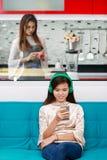 Fille regardant la mère blanche de smartphone faisant cuire dans la cuisine Images libres de droits