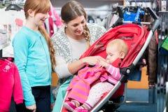Fille regardant la mère prenant soin de bébé dans la boutique images stock