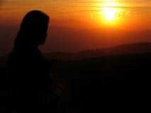 Fille regardant le coucher du soleil Photos stock