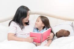Fille regardant le livre de lecture de mère sur le lit Photographie stock