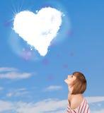 Fille regardant le nuage blanc de coeur sur le ciel bleu Photos stock