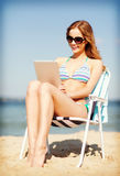 Fille regardant le PC de comprimé sur la plage Images stock