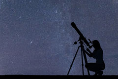 Fille regardant les étoiles avec le télescope Ciel de nuit étoilé image stock