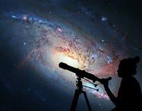 Fille regardant les étoiles avec le télescope Galaxie en spirale M106 photographie stock