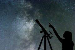 Fille regardant les étoiles Manière laiteuse de télescope image stock