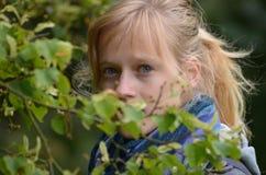 Fille regardant par des feuilles Photo libre de droits