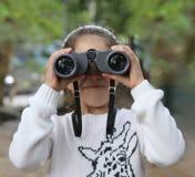 Fille regardant par des jumelles Images libres de droits