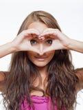 Fille regardant par les doigts en forme de coeur Photographie stock