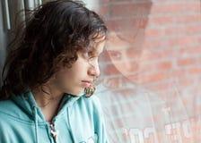 Fille regardant par une fenêtre Photos libres de droits