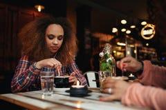 Fille remuant le café dans un café Photographie stock libre de droits