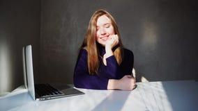 Fille renversante s'asseyant près de l'ordinateur portable et souriant, email de attente d'Angleterre banque de vidéos