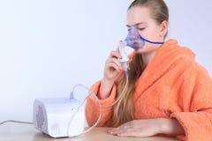 Fille respirant par un nébuliseur de vapeur D'isolement sur le fond blanc Photographie stock libre de droits