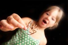 Fille retenant l'araignée brune par un patte et regard Photographie stock