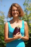 Fille retenant une grande aubergine Image stock