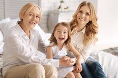 Fille riant dans l'étreinte de sa mère et grand-mère Images stock