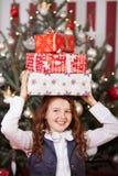 Fille riante avec des cadeaux de Noël sur sa tête Image libre de droits