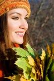 Fille riante avec des lames d'automne sur la nature photographie stock libre de droits