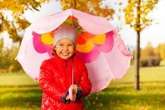 Fille riante avec le parapluie se tenant sous la pluie Image libre de droits