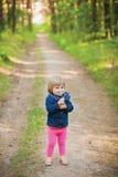 Fille riante d'enfant en bas âge dans la forêt avec des fleurs Images stock