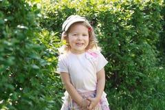 Fille riante de deux ans dans le chapeau plat de velours côtelé au fond vert de bosquet de jardin Photographie stock