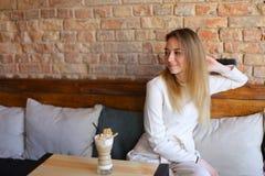 Fille riante s'asseyant sur la chaise près de la table en bois avec la tasse de cappuccino Image stock