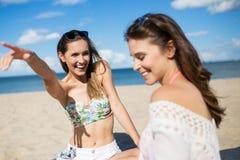 Fille riante s'asseyant sur la plage avec l'ami se dirigeant à quelque chose Photographie stock