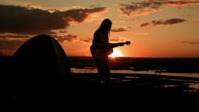 Fille romantique attirante jouant la guitare acoustique, au coucher du soleil près du camping sur la haute colline, silhouette banque de vidéos