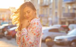 Fille romantique de brune avec les yeux fermés posant au fond de ville de tache floue avec des rayons du soleil L'espace pour le  photos libres de droits