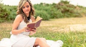 Fille romantique lisant un livre se reposant dehors Photo stock
