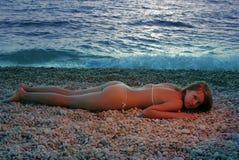 Fille rouge dans la lumière de coucher du soleil sur le rivage Images stock