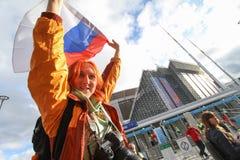 Fille rouge de fan avec le drapeau de la Russie près de l'arène de stade Photos stock