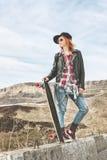 Fille rousse élégante dans un chapeau et des combinaisons de denim se tenant sur une bosse à la route dans les montagnes avec un  Photographie stock libre de droits