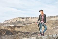 Fille rousse élégante dans un chapeau et des combinaisons de denim se tenant sur une bosse à la route dans les montagnes avec un  Image stock