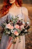 Fille rousse avec des taches de rousseur tenant un bouquet l'épousant photo stock