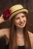 Fille rousse avec la fleur rouge photographie stock libre de droits