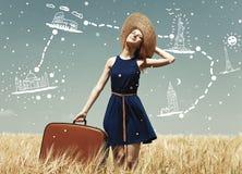 Fille rousse avec la valise au gisement de blé de mars Photo libre de droits